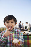 吃杯形蛋糕,在他的嘴的手指和看照相机的男孩 图库摄影