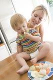 吃果子母亲蔬菜的婴孩 免版税库存图片