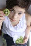 吃果子猕猴桃裁减圈子的少年男孩 免版税库存图片