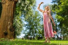 吃果子的俏丽的女孩在公园 图库摄影