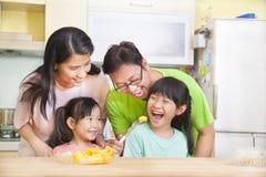 吃果子的愉快的家庭在厨房里 库存照片