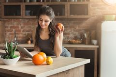 吃果子的愉快的少妇在厨房里 免版税库存照片