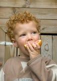 吃果子的男孩酸 免版税库存图片