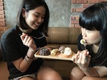 吃果仁巧克力和巧克力冰淇凌的亚裔逗人喜爱的少年妇女 免版税库存照片