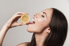 吃柠檬的少妇画象 免版税库存照片
