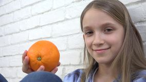 吃桔子果子的孩子在早餐,女孩孩子嗅到的健康食品厨房 股票录像