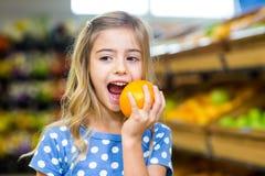 吃桔子的微笑的女孩 库存照片
