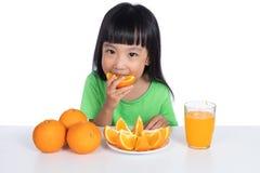 吃桔子的愉快的亚裔中国小女孩 库存图片