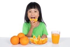 吃桔子的愉快的亚裔中国小女孩 免版税库存图片