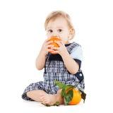 吃桔子的逗人喜爱的小孩 库存照片