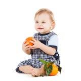 吃桔子的逗人喜爱的小孩 免版税库存图片