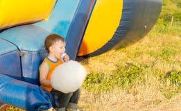 吃棉花糖果的年轻男孩坐在幻灯片附近 库存照片