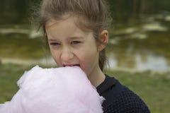 吃棉花糖的可爱的小女孩户外在夏天 库存照片