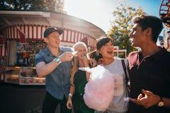 吃棉花糖的小组朋友在集市场所 免版税库存照片