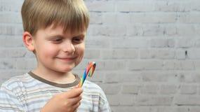 吃棒棒糖和微笑的逗人喜爱的小男孩 库存照片