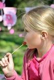 吃棒棒糖的逗人喜爱的白肤金发的小孩女孩 免版税库存图片