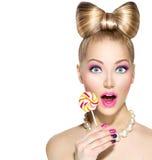吃棒棒糖的滑稽的女孩 库存图片