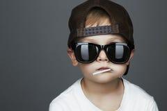 吃棒棒糖的滑稽的年轻男孩 太阳镜的孩子 免版税库存图片