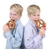 吃椒盐脆饼的两个男孩 库存图片