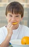 吃橙色片式的男孩 库存图片