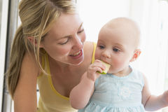 吃母亲的苹果婴孩 免版税库存图片