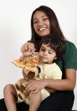吃母亲薄饼片式的女儿 免版税库存照片