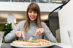 吃比萨的年轻女人画象 从wood-burning火炉的那不勒斯的比萨 在意大利trattoria的午餐 表 图库摄影