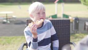 吃比萨的逗人喜爱的白肤金发的男孩在街道餐馆 股票视频