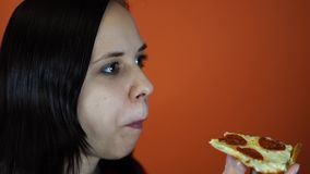 吃比萨,在橙色背景的特写镜头的妇女 女性享受一顿可口膳食 股票录像