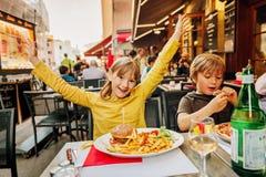 吃汉堡包用炸薯条和薄饼的愉快的孩子 免版税库存照片