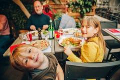 吃汉堡包用炸薯条和薄饼的愉快的家庭 免版税库存图片