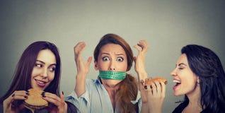 吃汉堡包的两名愉快的妇女看有测量的磁带的被注重的女孩在她的嘴附近 免版税库存照片