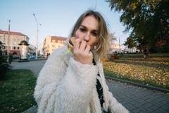 年轻吃汉堡包的时尚滑稽的妇女室外在街道上 图库摄影