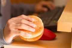 吃汉堡和使用计算机的年轻男孩 免版税图库摄影