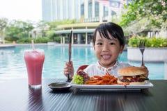 吃汉堡和炸薯条的亚裔矮小的中国女孩 免版税图库摄影