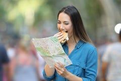 吃汉堡和读地图的妇女在度假 免版税库存照片