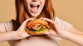 吃汉堡的一饥饿的年轻女人的接近的画象被隔绝在裸体背景 免版税库存图片
