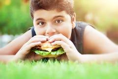吃汉堡的青少年的男孩 免版税图库摄影