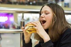 吃汉堡,背景商城娱乐中心的十几岁的女孩 免版税库存照片
