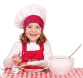 吃汤的小女孩厨师 免版税库存照片
