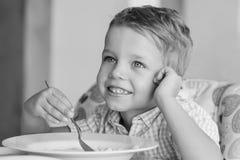 吃汤的愉快的小男孩 免版税库存照片