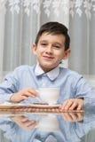 吃汤的男孩在厨房用桌上 免版税库存照片