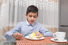 吃汤的男孩在厨房用桌上 库存图片