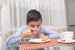 吃汤的男孩在厨房用桌上 图库摄影