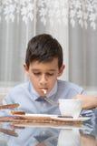 吃汤的男孩在厨房用桌上 库存照片