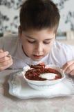 吃汤的男孩少年在厨房用桌上 免版税图库摄影