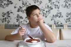 吃汤的男孩少年在厨房用桌上 免版税库存照片