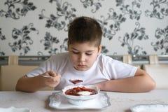 吃汤的男孩少年在厨房用桌上 免版税库存图片