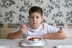 吃汤的男孩少年在厨房用桌上 库存图片