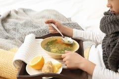 吃汤的病的小男孩治疗寒冷在床上 免版税图库摄影